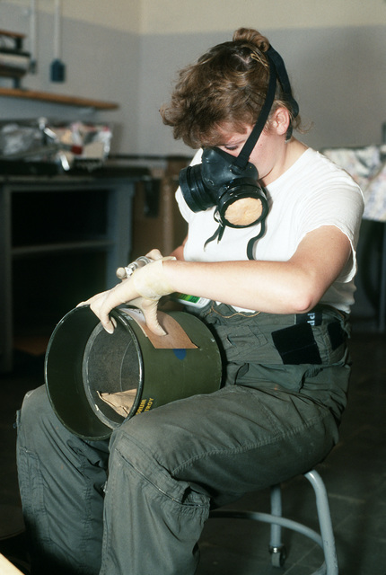 Mineman 3rd Class (MN3) Trudy Praytor paints a label on an arming device intended for use in a Mark 52 mine.  Praytor is assigned to Mobile Mine Assembly Group Unit 5