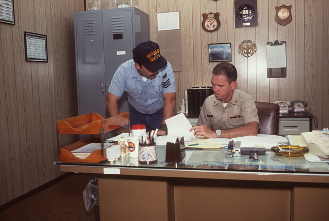 Mineman First Class (MN1) Vincent Price, a member of the Mobile Mine Assembly Group Unit 5 quality assurance team, talks with SENIOR CHIEF Mineman (MNCS) Larry Moir, the command senior chief petty officer