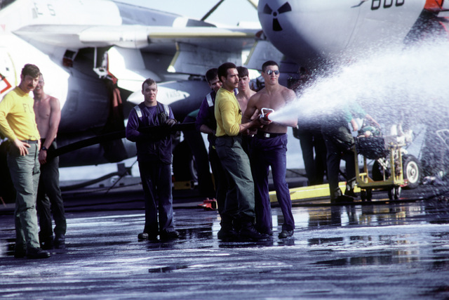 A petty officer assists crew members in hosing off the aircraft carrier USS KITTY HAWK (CV-63)
