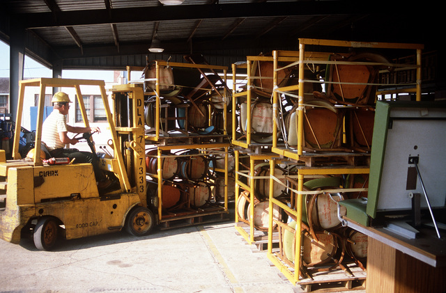 A forklift moves racks of chairs that are being stored outside beneath a shelter at the Defense Property Disposal Office