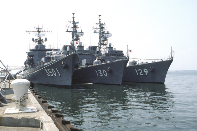A starboard bow view of the Japanese training ship KATORI (TV-3501), the destroyer MATSUYUKI (DD-130) and the destroyer YAMAYUKI (DD-129) moored at a pier. The ships, part of the Japanese Maritime Self-Defence Force, are visiting Naval Operating Base, Norfolk