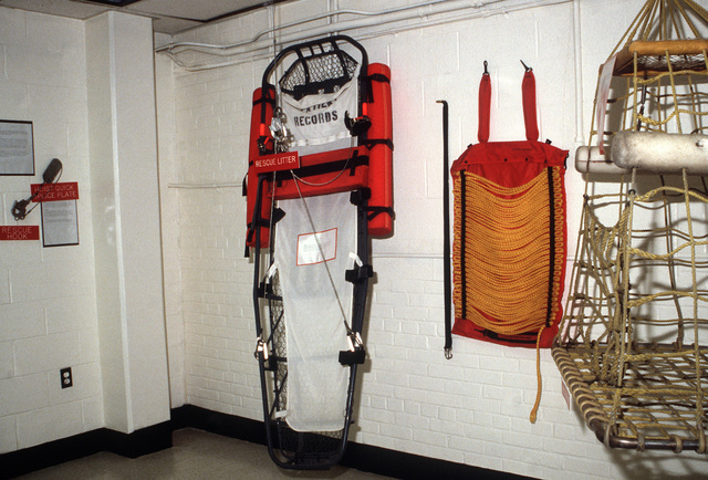 A litter, a cage and other rescue devices are displayed at the station's Aviation Physiology Training Unit