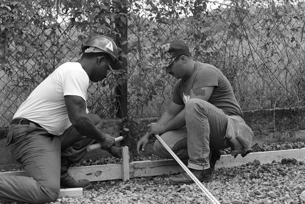 Builder 1ST Class (BU-1) Steve Mayes, left, and Building Constructionman (BCSN) Paul Beck, both of the Naval Mobile Construction Battalion 133 (NMCB-133), drive a wooden stake to support a concrete form while participating in a civic action project