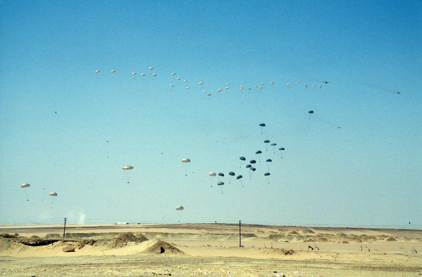 Paratroopers jump from C-130 Hercules aircraft during the multinational, joint service Exercise BRIGHT STAR'87