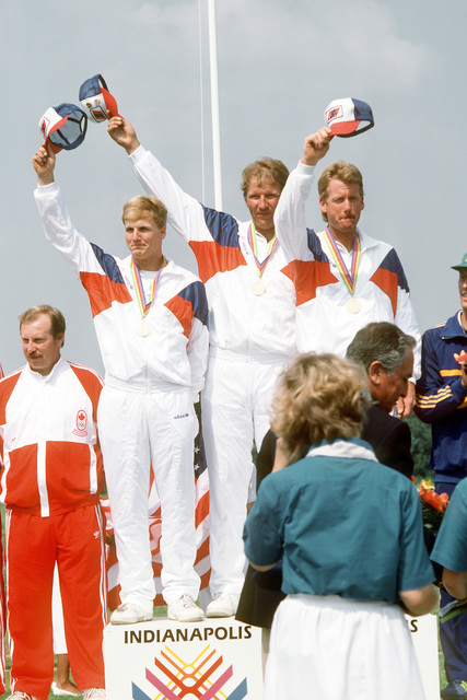SPEC. 4 George Haas, left, SPEC. 4 Ken Blasi, center, and the third member of the U.S. trap shooting team wave from the winner's platform after being awarded gold medals for their efforts in the 10th Annual Pan American Games. Exact Date Shot Unknown