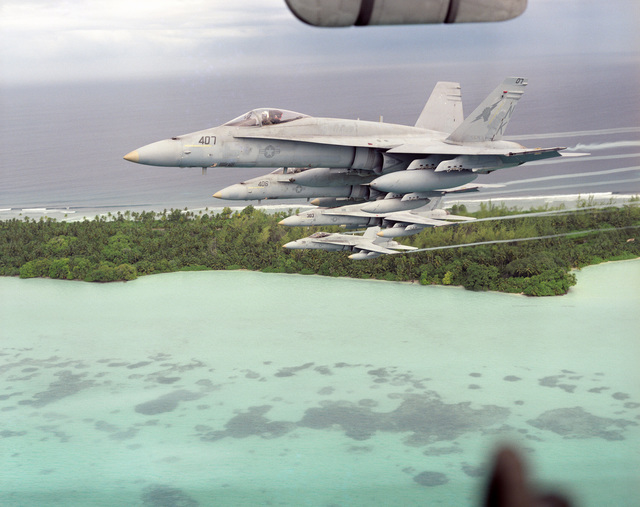 A four ship formation of US Navy (USN) F/A-18A Hornets, in flight over Diego Garcia, British Indian Ocean Territory (IOT). The group is made up of aircraft from Strike Fighter Squadron 25 (VFA-25), Fist of the Fleet, (400 series), and Strike Fighter Squadron 113 (VFA-113), Stingers, (300 series)