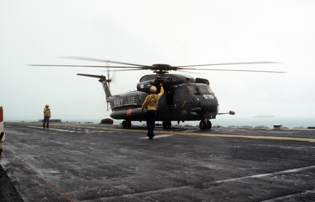 A plane director signals instructions to the pilot of a CH-53E Sea Stallion helicopter as it prepares for lift-off from the deck of the amphibious assault ship USS GUADALCANAL (LPH 7). The ship is preparing to depart for the Persian Gulf