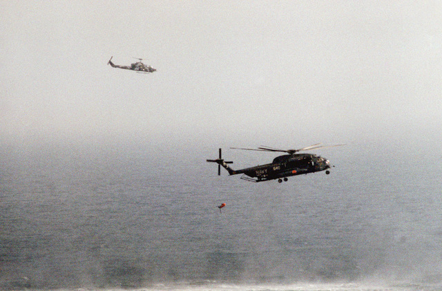 A right side view of a Helicopter Mine Countermeasures Squadron 14 (HM-14) RH-53D Sea Stallion helicopter towing a lightweight magnetic sweep during mine contermeasures operations. The helicopter is assigned to the amphibious assault ship USS GUAM (LPH 9). Note: Sixth view in a series of six