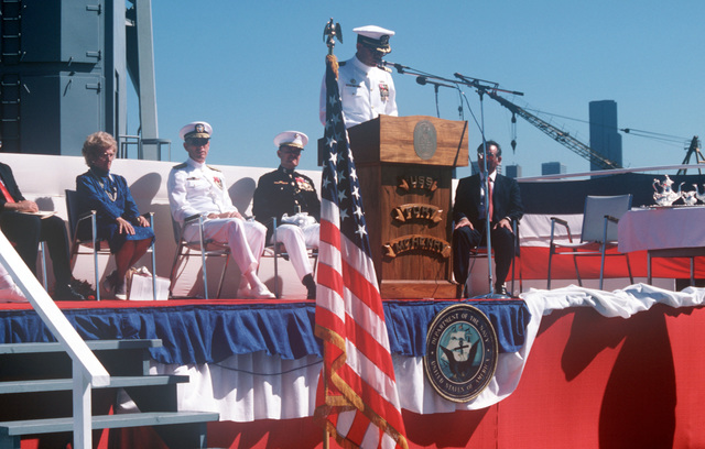 Commander (CDR) George S. Rhodes, commanding officer, speaks during the ship's commissioning of the dock landing ship USS FORT MCHENRY (LSD 43). Seated on the platform, left to right, are: Paul A. Schneider, executive director, Amphibious, Auxiliary, Line and Sealift Ships Directorate, Naval Sea Systems Command; Representative Helen D. Bentley, Democrat-Maryland (MD), Vice Admiral (VADM) George W. Davis Jr., commander, Naval Surface Force, US Atlantic Fleet; Major General (MGEN) Carl E. Mundy, Jr., USMC; and Joseph R. Santosuosso, president, Lockheed Shipbuilding Co