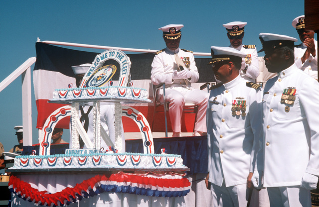 Distinguished guests and crew members look over the commissioning cake for the dock landing ship USS FORT MCHENRY (LSD 43). They are, left to right, front row: Commander (CDR) George S. Rhodes, ship's commanding officer; MASTER CHIEF Boatswain's Mate Jesse J. Holloway, command master chief; top row, Chaplain (Captain (CAPT)) Jack D. Graham, CAPT Phillip F. Grasser, supervisor of shipbuilding, Seattle, Washington; Rear Admiral (RADM) Joseph P. Reason, commander, Naval Base, Seattle, Washington