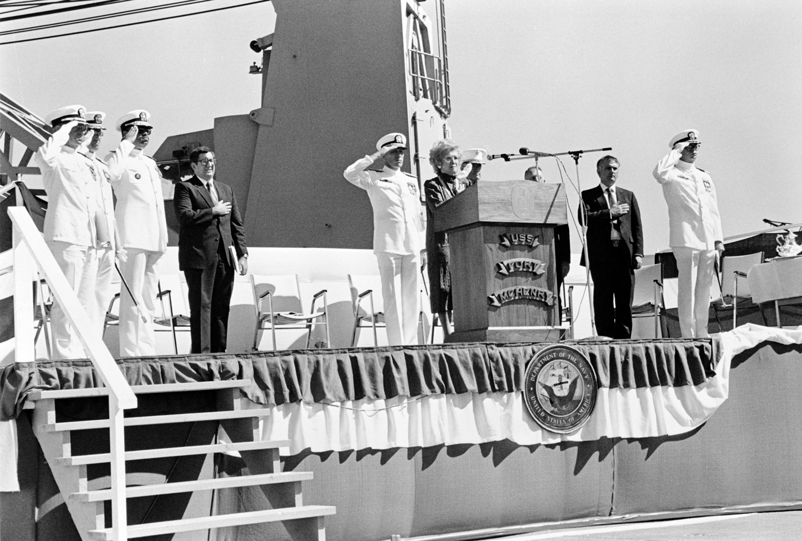 Distinguished guests pay honor to the flag during the commissioning of the dock ship USS FORT MCHENRY (LSD 43).  They are, left to right:  Captain (CAPT) J. Graham, USN, Chaplain, CAPT P. Grasser, Rear Admiral (RDML) (lower half) J.P. Reason, P.A. Schneider, Naval Sea Systems Command; Vice Admiral (VADM) G.W. Davis Jr., commander, Naval Surface Force, Pacific; Representative Helen D. Bentley, Republican-Maryland, Major General (MGEN) C.E. Mundy Jr., US Marine Corps (USMC); Retired Colonel (COL) E.E. Shoults, USMC; J.R. Santosuosso, president, Lockheed Shipbuilding Co.; Commander (CDR) G.S. Rhodes, commanding officer, USS FORT MCHENRY (LSD 43)