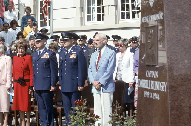 Mrs. Jessie Puffer, Mrs. Evelyn (Lindsey) Rhinehart, Major General (MGEN) Richard Pascoe, Colonel (COL) Ralph S. Rothstein and Lyle Lindsey stand near a memorial to Captain Darrell L. Lindsey during the dedication ceremony for Lindsey Air Station. Lindsey, an officer in the US Army Air Corps during World War II, was awarded the medal of honor posthumously for his role in the successful destruction of the L'Isle Adam Railraod Bridge over the Seine in enemy-occupied France