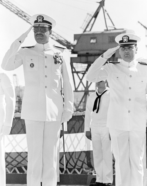 Rear Admiral (RDML) (lower half) Joseph P. Reason, commander, Naval Base, Seattle, salutes during the commissioning of the dock landing ship USS FORT MCHENRY (LSD 43)