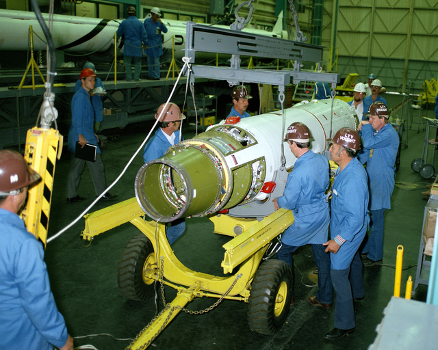 The third stage of a Scout rocket is moved into position to be mated with the second stage by technicians in Building 960