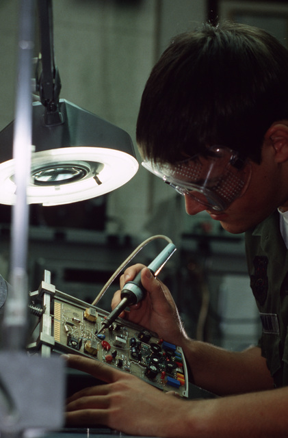 AIRMAN First Class (A1C) David Bowman, a member of the 1961st Communications Group, uses a soldering iron to repair a circuit board.  The 1961st recently won the Major General Harold M. McClelland Award for communications excellence for the third time in five years