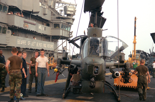 Crewmen service an AH-1 Sea Cobra helicopter on the flight deck of the amphibious assault ship USS GUADALCANAL (LPH-7) prior to the ship's entry into the Persian Gulf. The helicopter is armed with an AIM-9 Sidewinder missile on the right weapons pylon