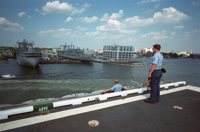 A crew member aboard the US Navy (USN) Aircraft Carrier USS JOHN F. KENNEDY (CV 67) looks across the river at the Ready Reserve Force Ships SS BANNER (T-AK 5008), left, and SS CAPE CANSO (T-AK 5037)
