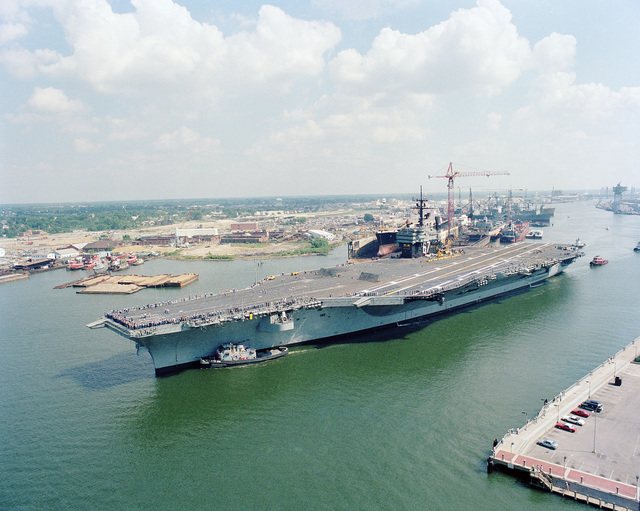 A port bow view of the US Navy (USN) Aircraft Carrier USS JOHN F. KENNEDY (CV 67) being assisted by large harbor tugs as it leaves the Norfolk Naval Shipyard on its way to Norfolk Naval Operating Base