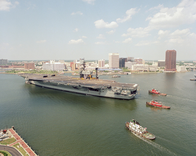 A port quarter view of the US Navy (USN) Aircraft Carrier USS JOHN F. KENNEDY (CV 67) being assisted by large harbor tugs as it leaves the Norfolk Naval Shipyard