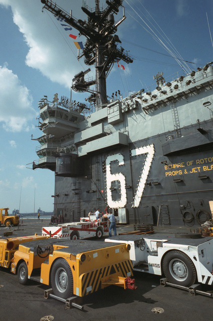 Crash vehicles and MD-3A tow tractors are parked next to the island of the US Navy (USN) Aircraft Carrier USS JOHN F. KENNEDY (CV 67)