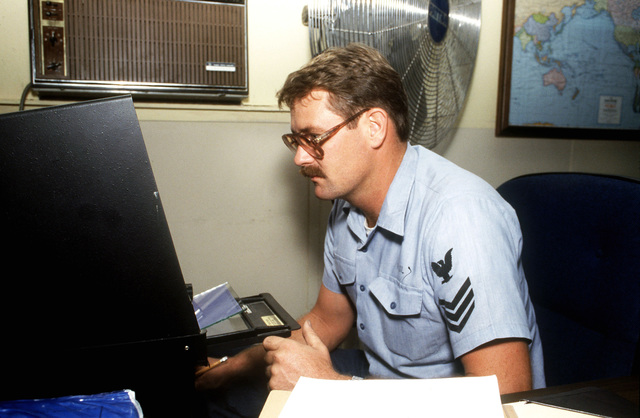 Electrician's Mate 1ST Class Rex Paul of the Light Airborne Multi-Purpose System (LAMPS) Support Detachment at the air station loads a microfiche into a reader to crossreference stock numbers