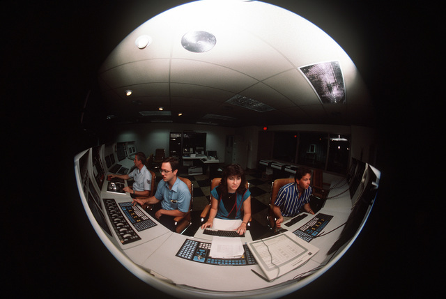 Fisheye lens view of, from left: TECH. SGT. Paul Scharfenberger, DOPD/Propulsion Testing; Doug Dixon, instrumentation controls engineer; Marilyn Felch, controls system engineer and Joel Wood, work element engineer. The engineers are reviewing the TAC computer system check list of the T-2 Test Cell Westinghouse Test Area Control 2D03451A computer at the Arnold Engineering Development Center