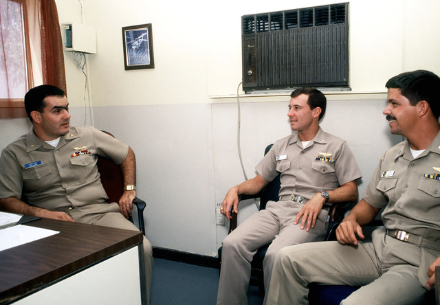 Lieutenant Commander Kim Shepard, left, officer in charge of the Light Airborne Multi-Purpose System (LAMPS) Support Detachment at the air station, talks with Lieutenant Dave Piccone, center, and Lieutenant John Roberti. Piccone and Roberti, both from Light Helicopter Anti-submarine Squadron 34 (HSL-34), are LAMPS pilots deployed aboard the destroyer USS COMTE DE GRASSE (DD 974)