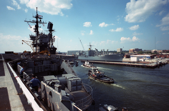 The large harbor tug MENOMINEE (YTB 790) accompanies the aircraft carrier USS JOHN F. KENNEDY (CV 67) while en route to Naval Operating Base, Norfolk.  The combat stores ship USS SAN DIEGO (AFS 6) is in the background