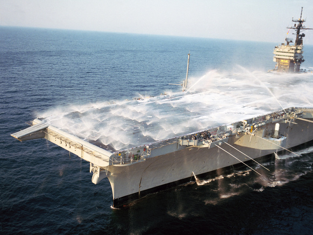 A port bow view of the aircraft carrier USS JOHN F. KENNEDY (CV 67) as the ship's aqueous film-forming foam (AFFF) system is tested during sea trials