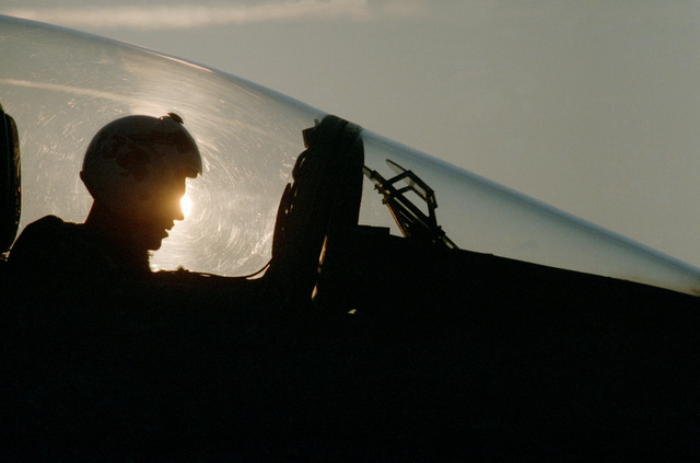 A silhouetted view of a pilot sitting in the cockpit of a Strike Fighter Squadron 106 (VFA-106) F/A-18A Hornet aircraft prior to an early morning flight