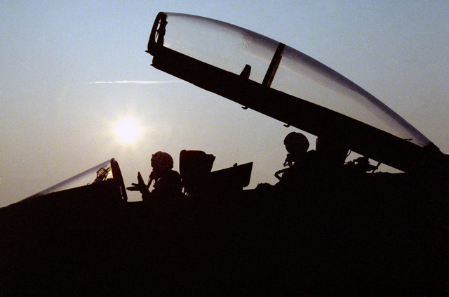 A silhouetted view of two pilots sitting in the cockpit of a Strike Fighter Squadron 106 (VFA-106) TF/A-18A Hornet aircraft prior to an early morning flight.  The pilot in the front seat is signaling instructions to a plane captain