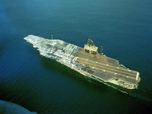 An aerial port quarter view of the aircraft carrier USS JOHN F. KENNEDY (CV 67) as the ship's aqueous film-forming foam (AFFF) system is tested on the forward section of the flight deck during sea trails