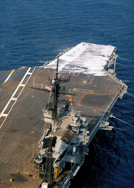 An aerial starboard quarter view of the aircraft carrier USS JOHN F. KENNEDY (CV 67) as the ship's aqueous film-forming foam (AFFF) system is tested on the forward section of the flight deck during sea trails