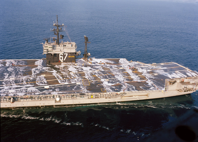 An aerial view of the stern half of the aircraft carrier USS JOHN F. KENNEDY (CV 67) as the ship's aqueous film-forming foam (AFFF) system is tested during sea trails