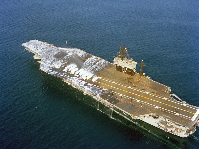 The aerial port quarter view of the aircraft carrier USS JOHN F. KENNEDY (CV 67) as the ship's aqueous film-forming foam (AFFF) system is tested during sea trials