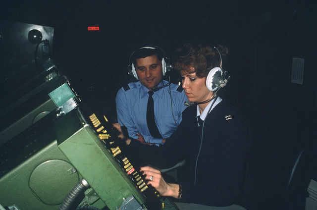 US Air Force air traffic control officer Captain (CPT) Susanne Hechinger coordinates air traffic from a controller station while British Flight Lieutenant (LT) Mark Wordley looks on at the RAF Watton eastern radar installation for air traffic control operations. The base is jointly used by the British and the US Air Force/Army