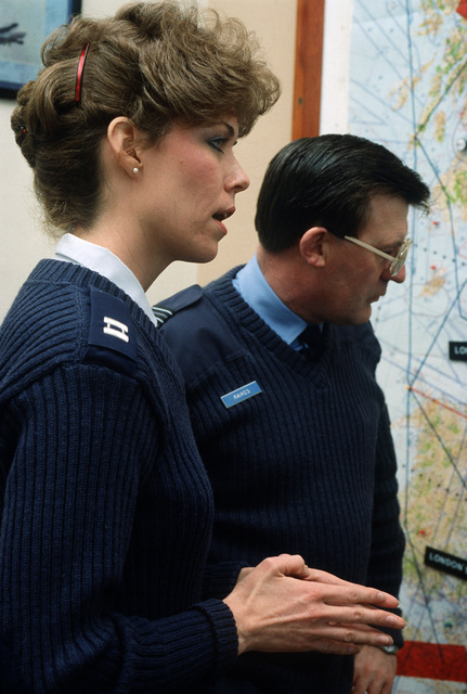 US Air Force air traffic control officer Captain (CPT) Susanne Hechinger examines a map with Colonel (COL) Peter Raikes, Royal Air Force (RAF), at the RAF Watton eastern radar installation for air traffic control operations. The base is jointly used by the British and the US Air Force/Army