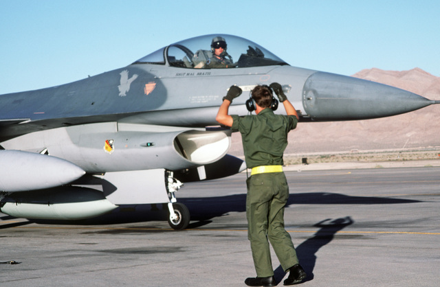 A member of the 428th Tactical Fighter Squadron signals instructions to the pilot of an F-16 Fighting Falcon aircraft taxiing along the flight line.  The aircraft is among 24 F-16s and 400 Air Force personnel that are departing for Ramstein Air Base, West
