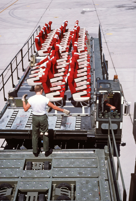 A member of the 554th Combat Support Group directs a K-loader carrying passenger seats to a KC-10A Extender aircraft.  These and other pieces of equipment and supplies are being transported to Ramstein Air Base, West Germany, for use in the short-term tac