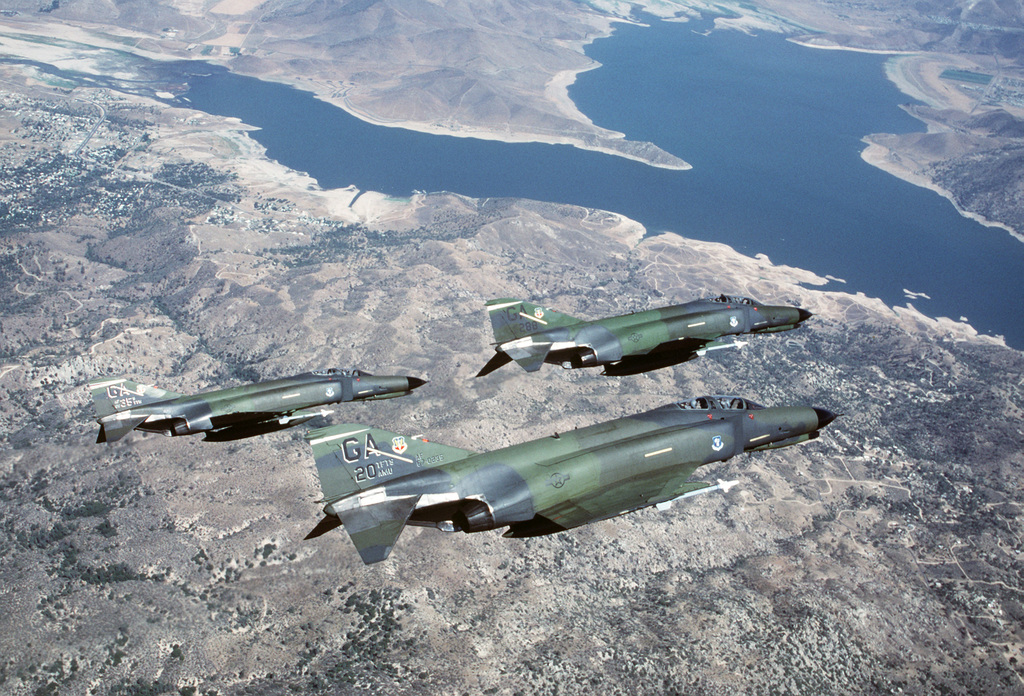 An air-to-air right side view of three F-4E Phantom II aircraft from the 35th Tactical Training Wing in formation over Lake Isabella.  The aircraft are armed with AIM-9 Sidewinder missiles