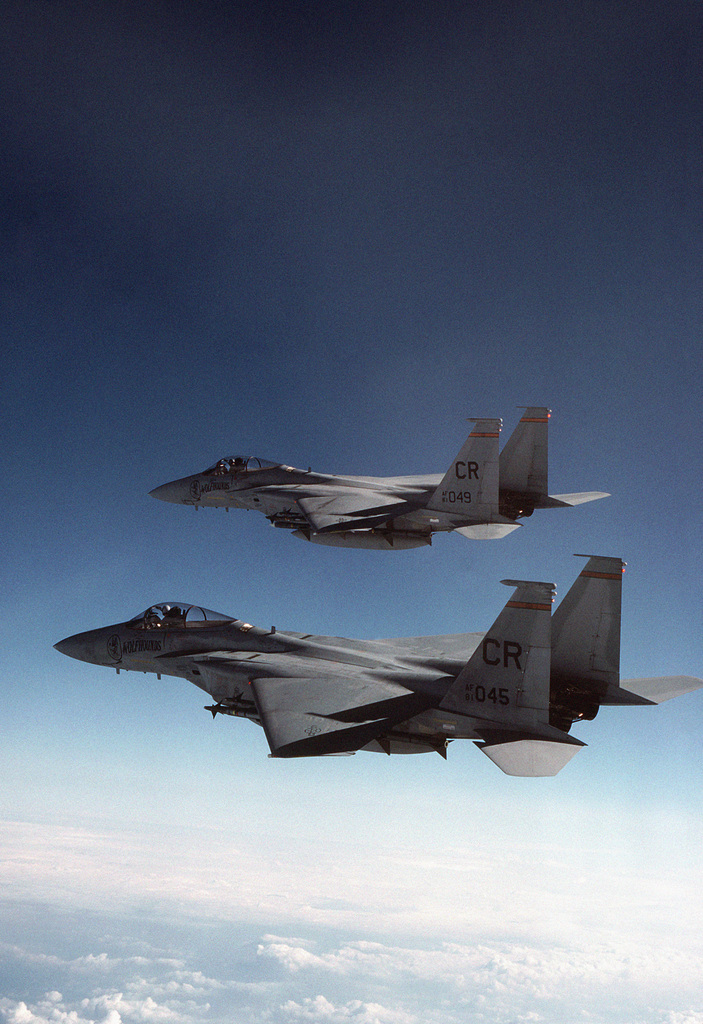 An air-to-air left side view of two 32nd Tactical Fighter Squadron (TFS) F-15C Eagle aircraft carrying a full load of AIM-9 Sidewinder and AIM-7 Sparrow missiles.  Members of the 32nd TFS are piloting the aircraft during a Zulu alert mission designed to protect Northern NATO nations from possible attack.  The 32nd TFS is the only USAF squadron to bear the official crest of the Queen of the Netherlands painted on the side of its F-15C fighter aircraft
