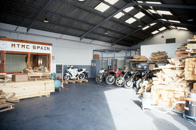 Motorcycles stand inside the privately owned vehicle (POV) warehouse of the Military Traffic Management Command, Transportation Terminal Unit - Spain