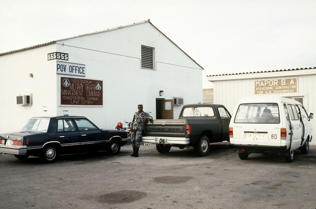 Sergeant Ronaldo V. Harrison stands in front of Building 555 of the Military Traffic Management Command, Transportation Terminal Unit - Spain, which houses the privately owned vehicle (POV) office