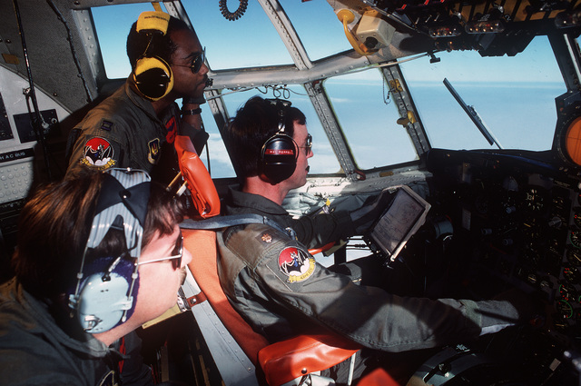 """Technical Sergeant (TSGT) Kenneth Hiller, flight engineer, Captain (CPT) Griffin Drees, flight evaluator, both from the 43rd Electronic Combat Squadron, and Major (MAJ) John Ferrell, pilot, 66th Electronic Combat Wing, watch the horizon from the cockpit of an EC-130H Hercules aircraft for a KC-135 Stratotanker aircraft that is to refuel them.  The EC-130H""""Compass Call""""aircraft is based at Sembach Air Base, Germany.  Its mission is to provide electronic countermeasures (ECM) to reduce the enemy's capability to wage war"""