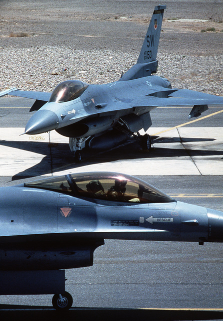 A 33rd Tactical Fighter Squadron F-16 Fighting Falcon aircraft taxis on the runway as another F-16 stands by on the flight line during Exercise SHADOW HAWK'87, a phase of BRIGHT STAR'87.  The US Central Command exercise represents a Joint Chiefs of STAFF