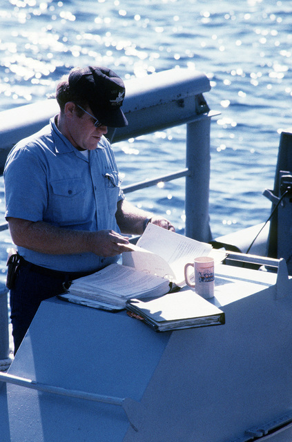 A crew member checks a safety manual prior to an exercise aboard the ocean minesweeper USS ILLUSIVE (MSO-448). The ILLUSIVE is one of three minesweepers being towed to the Persian Gulf by the salvage ship USS GRAPPLE (ARS-53) to support U.S. Navy escort operations