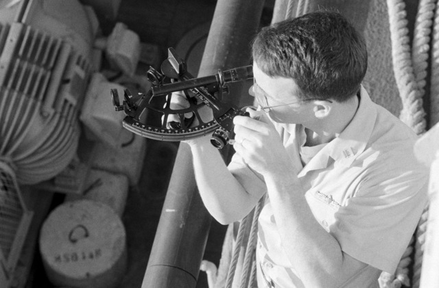 A crew member uses a sextant aboard the ocean minesweeper USS ILLUSIVE (MSO 448). The ILLUSIVE is one of three minesweepers being towed to the Persian Gulf to support US Navy escort operations