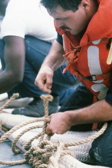 A crewman prepares hemp stays on the loops of the main tow rope on the fantail of the salvage ship USS GRAPPLE (ARS 53).  The GRAPPLE is towing three minesweepers to the Persian Gulf to support US Navy escort operations