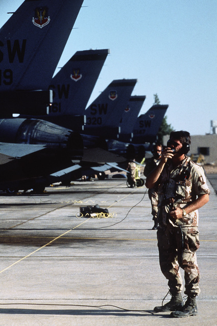 A flight line crewman communicates with the pilot of a 363rd Tactical Fighter Wing F-16 Fighting Falcon aircraft during Exercise SHADOW HAWK'87, a phase of BRIGHT STAR'87.  The US Central Command exercise represents a Joint Chiefs of STAFF effort to evalu