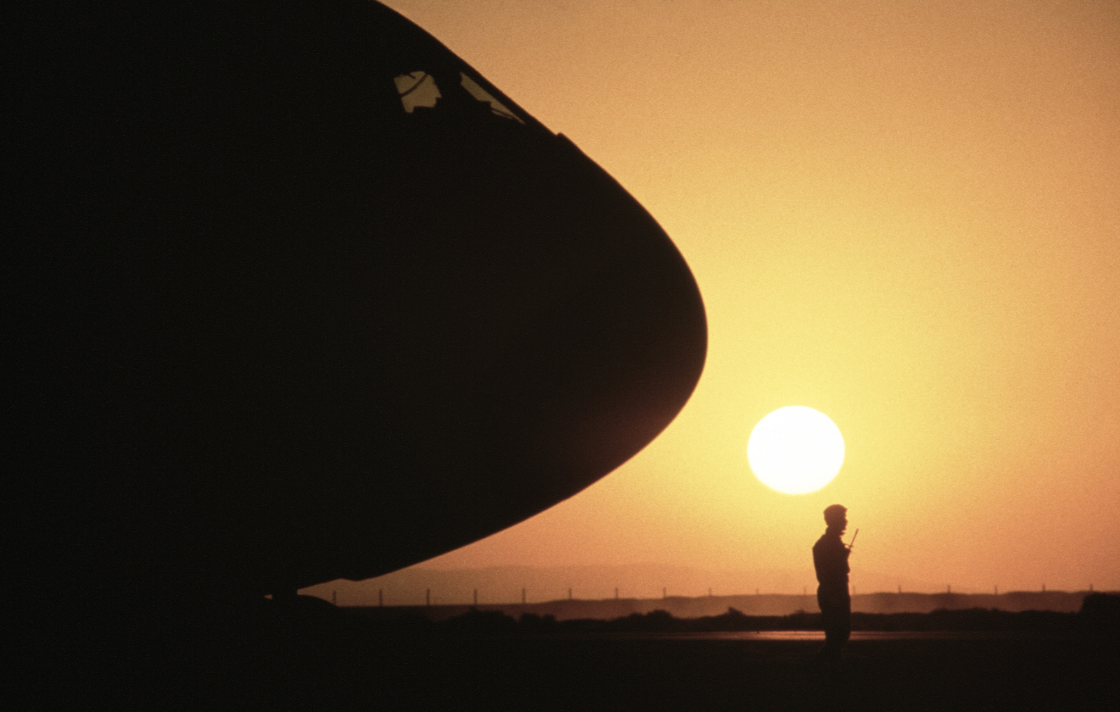 A member of the Jordanian military is silhouetted by the setting sun as he guards a 437th Military Airlift Wing C-141B Starlifter aircraft during Exercise SHADOW HAWK'87, a phase of BRIGHT STAR'87.  The US Central Command/Joint Chiefs of STAFF exercise pr